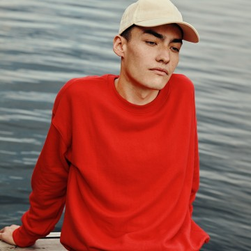 Man sitting close to water, wearing a bright red sweater
